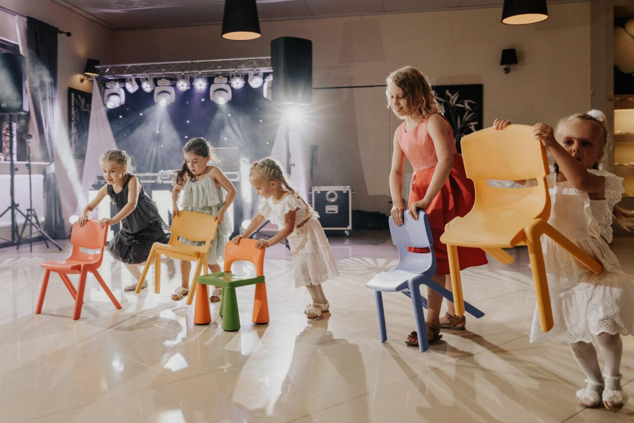 dziewczynki biegające z krzesłami po sali weselnej