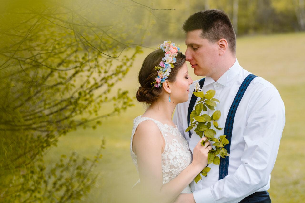pan młody całuje żonę pod drzewem na tle polany Bieszczadów