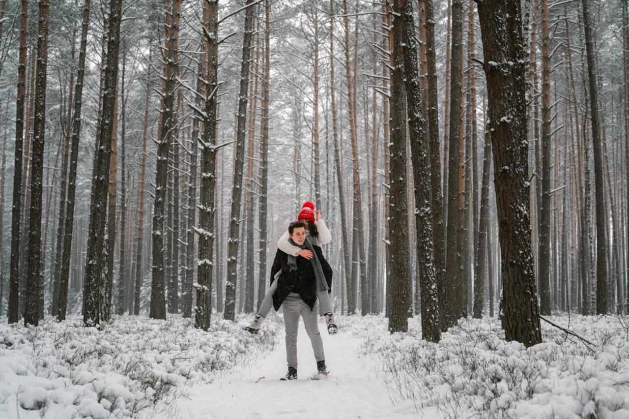 para zakochanych na tle śnieżnego krajobrazu lasu
