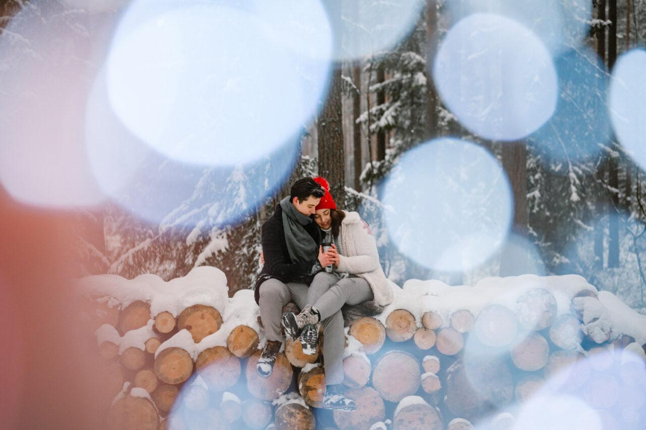 zakochana para siedzi na pniach ściętych drzew zimą