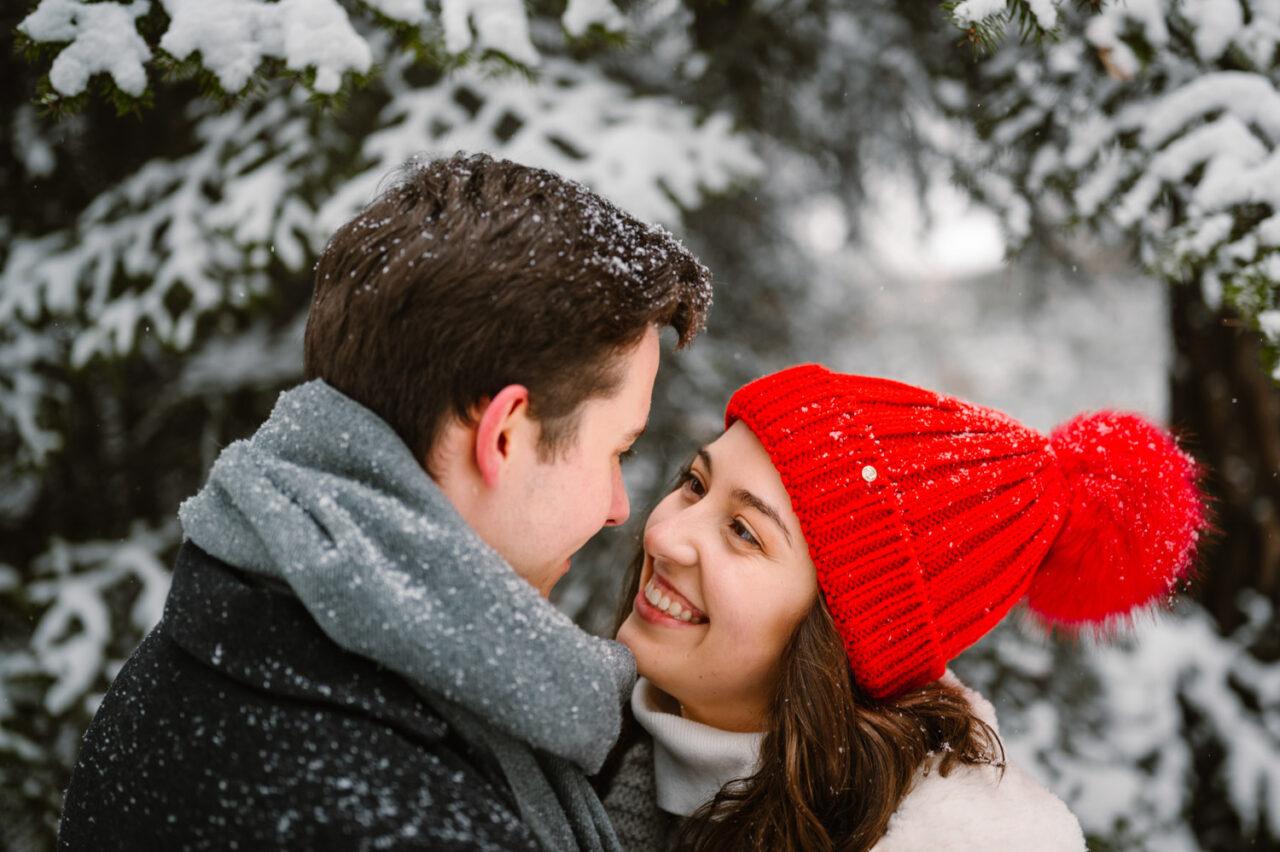 uśmiechnięta zakochana para w lesie zimą
