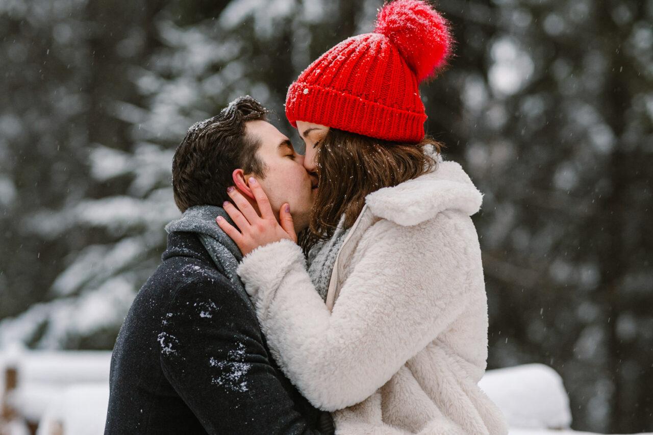 pocałunek zakochanej pary w lesie zimą
