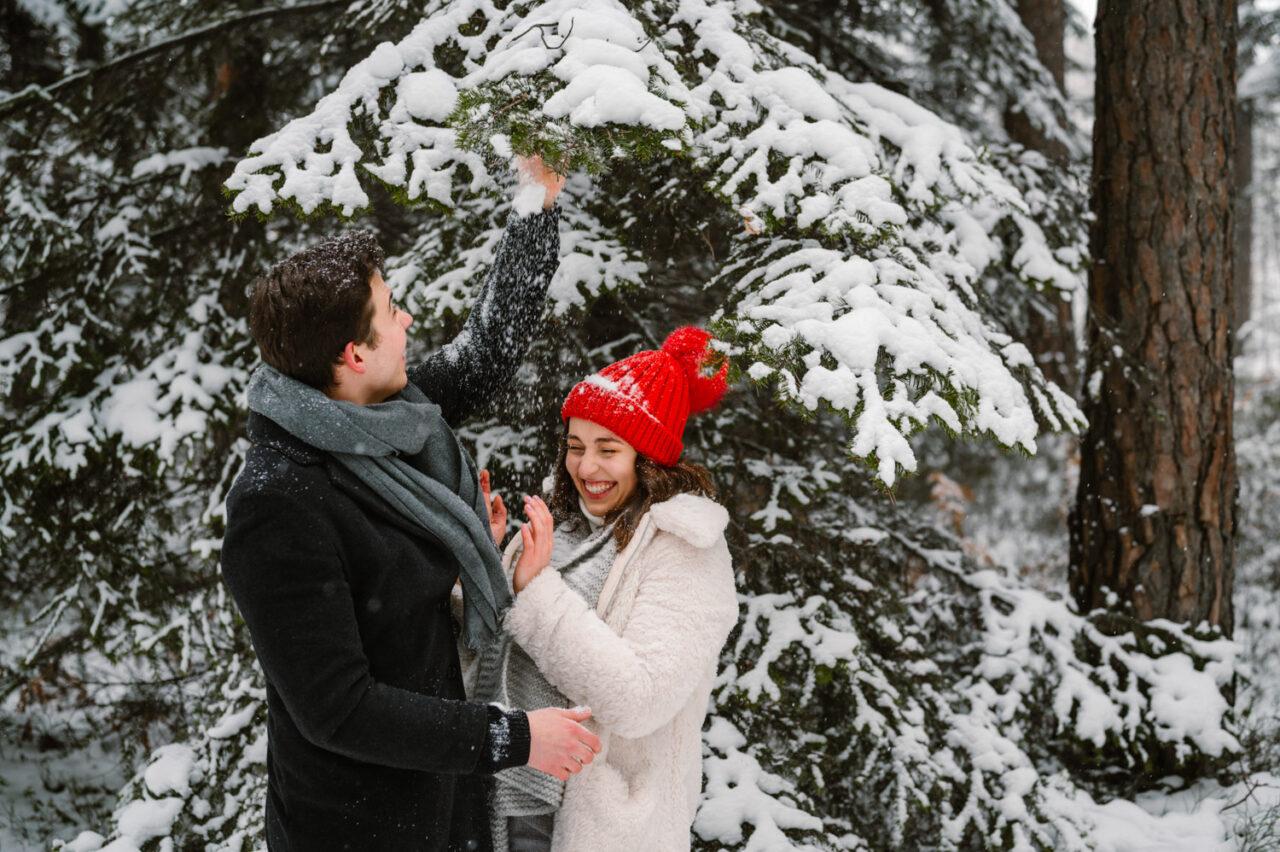 chłopak obsypuje dziewczynę śniegiem z drzew