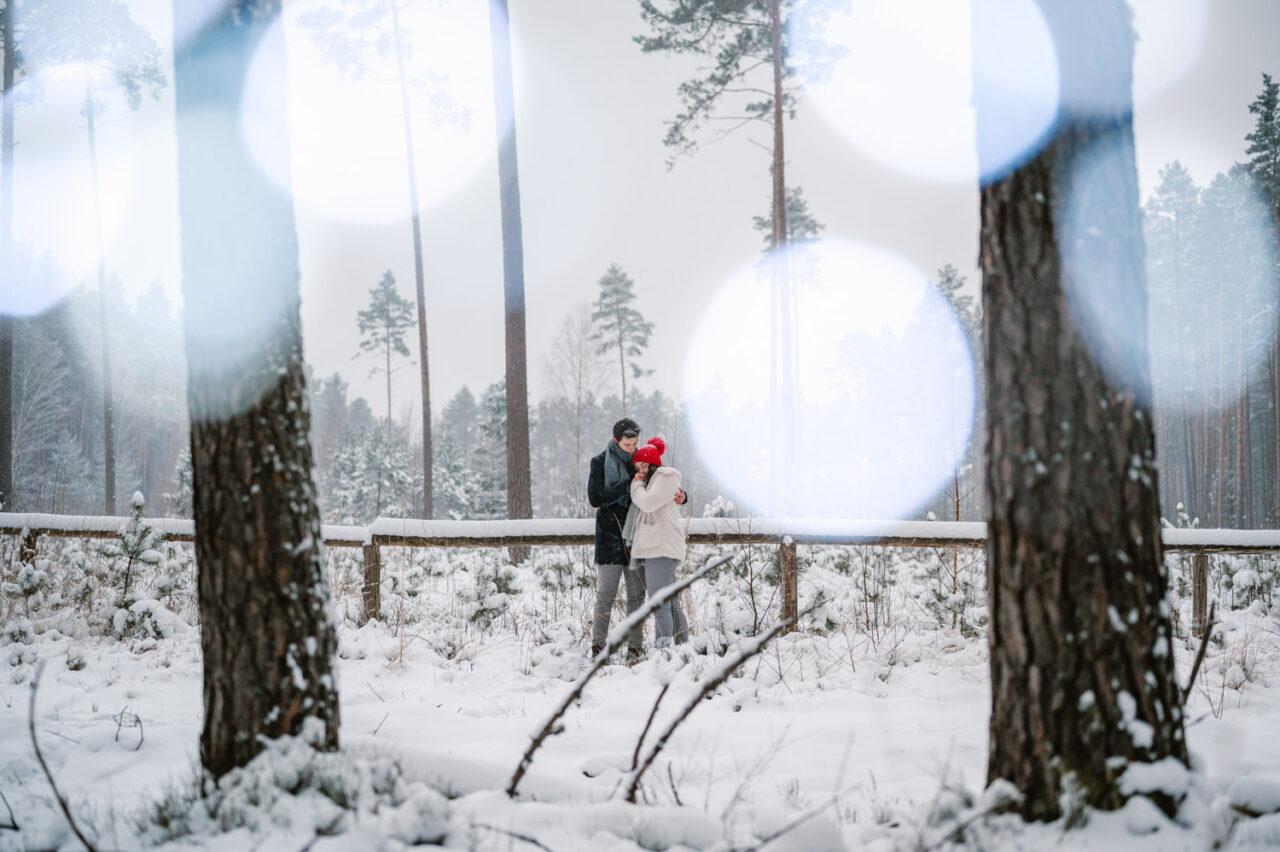 para zakochanych przytula się na tle zaśnieżonego lasu