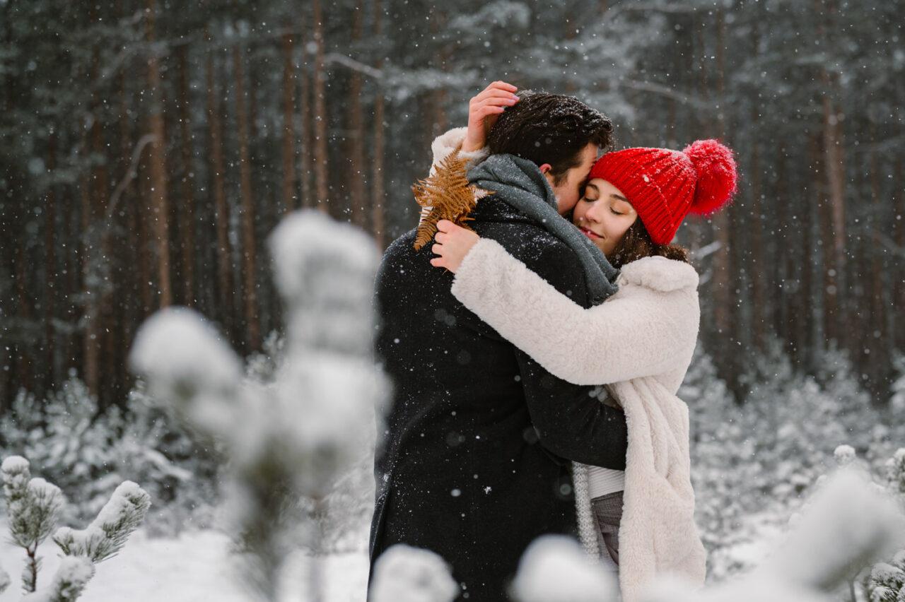 dziewczyna przytula chłopaka na tle zimowego lasu