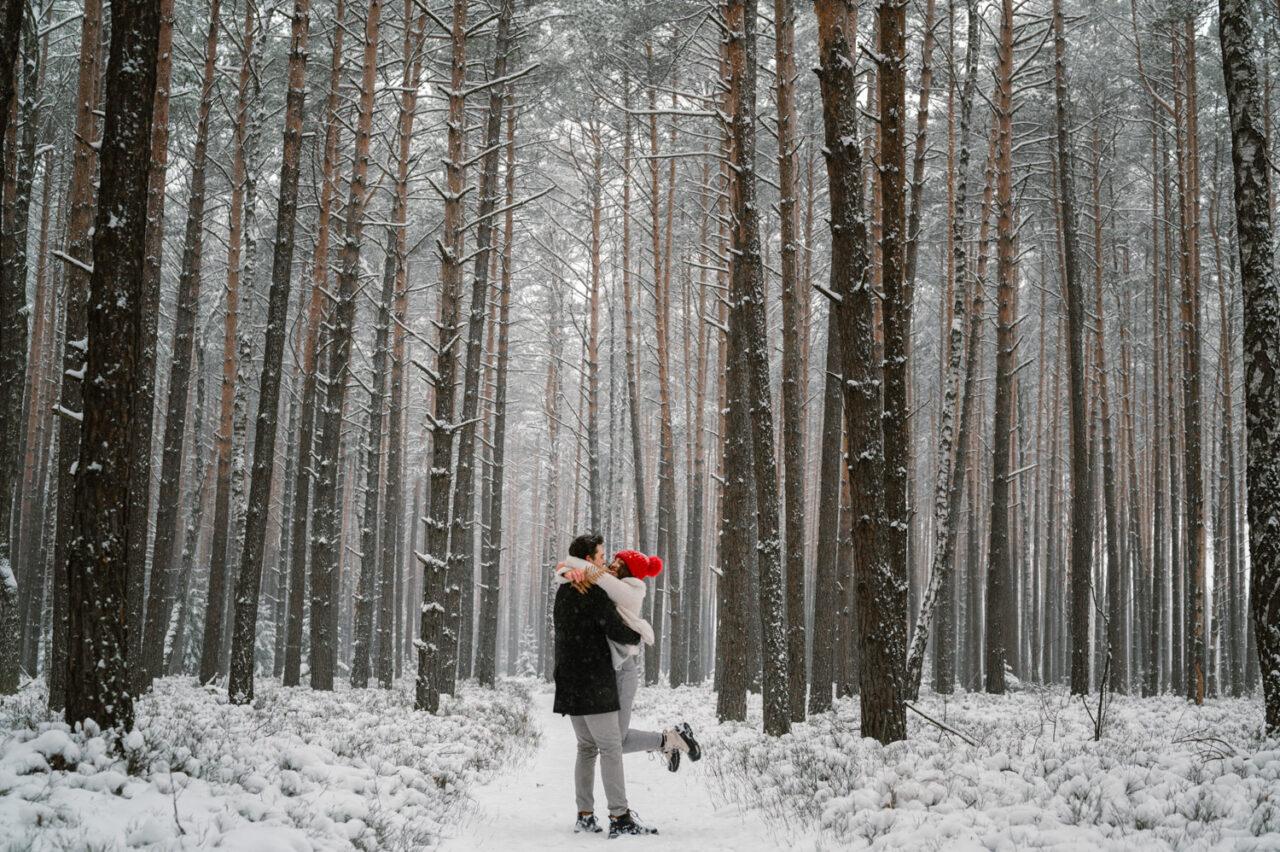 para zakochanych tańczy na tle zimowego lasu