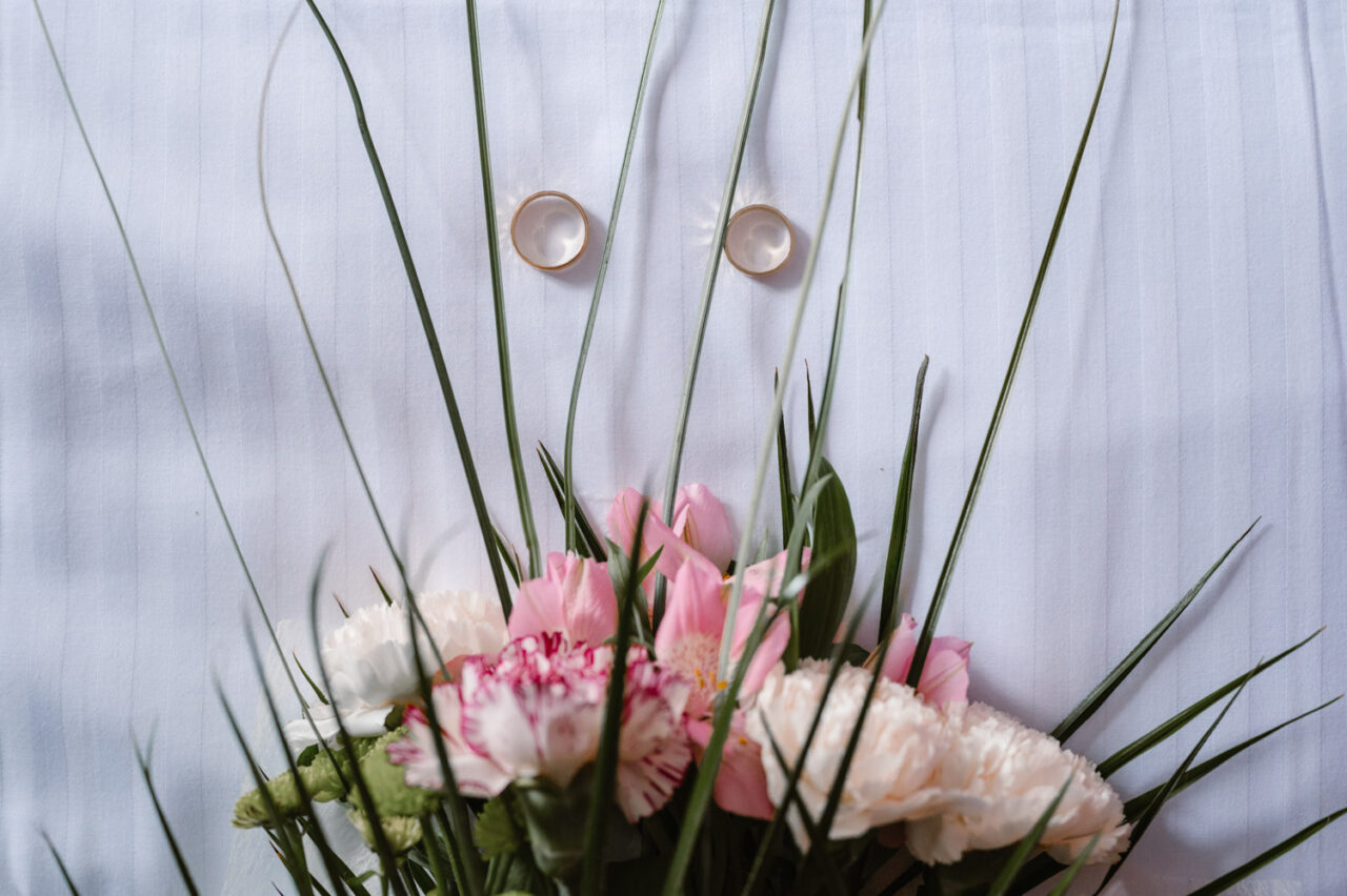 złote obrączki ślubne i fragment bukietu