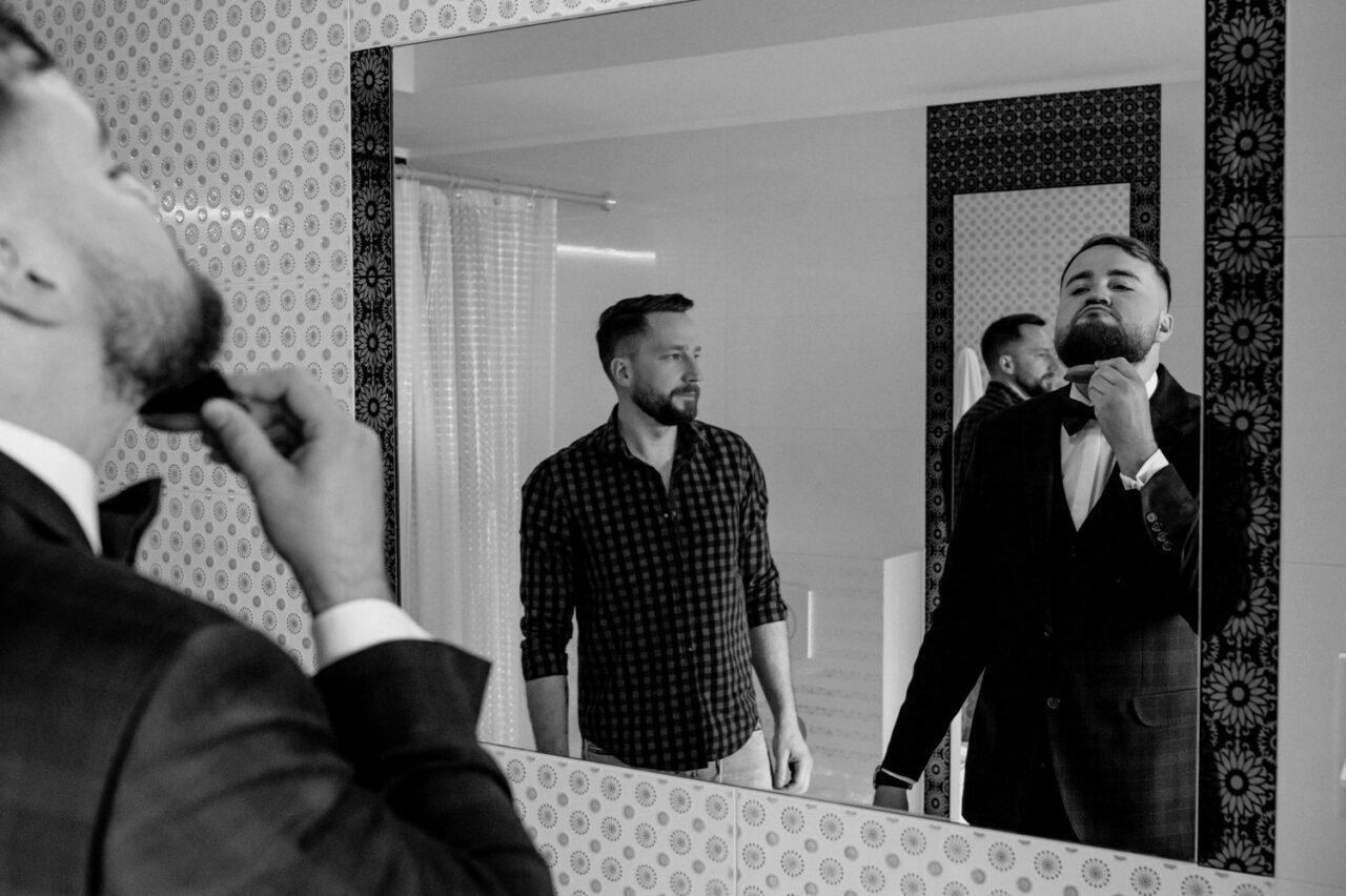 pan młody czesze brodę przed lustrem