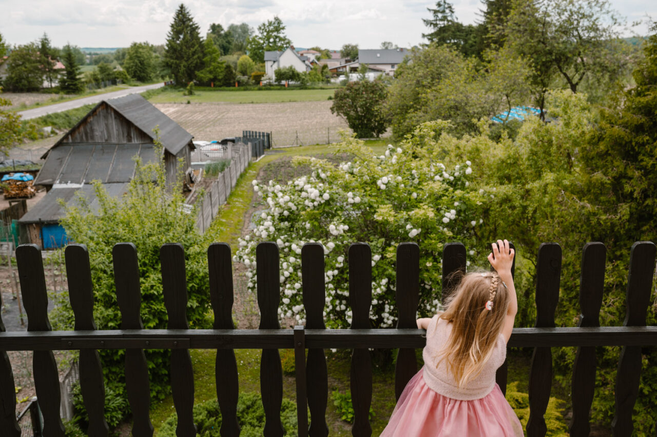 dziewczynka spogląda zza drewnianego płotku