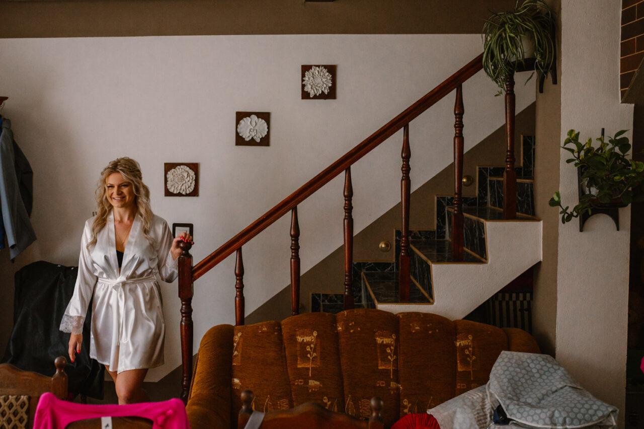 panna młoda w szlafroku przy schodach
