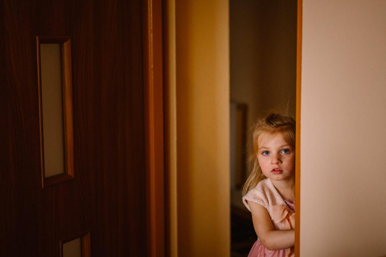 dziewczynka nieśmiało spoglądająca zza drzwi