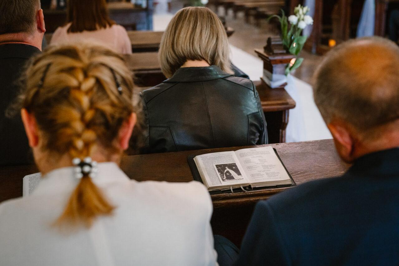 goście ślubni w kościele modlą się