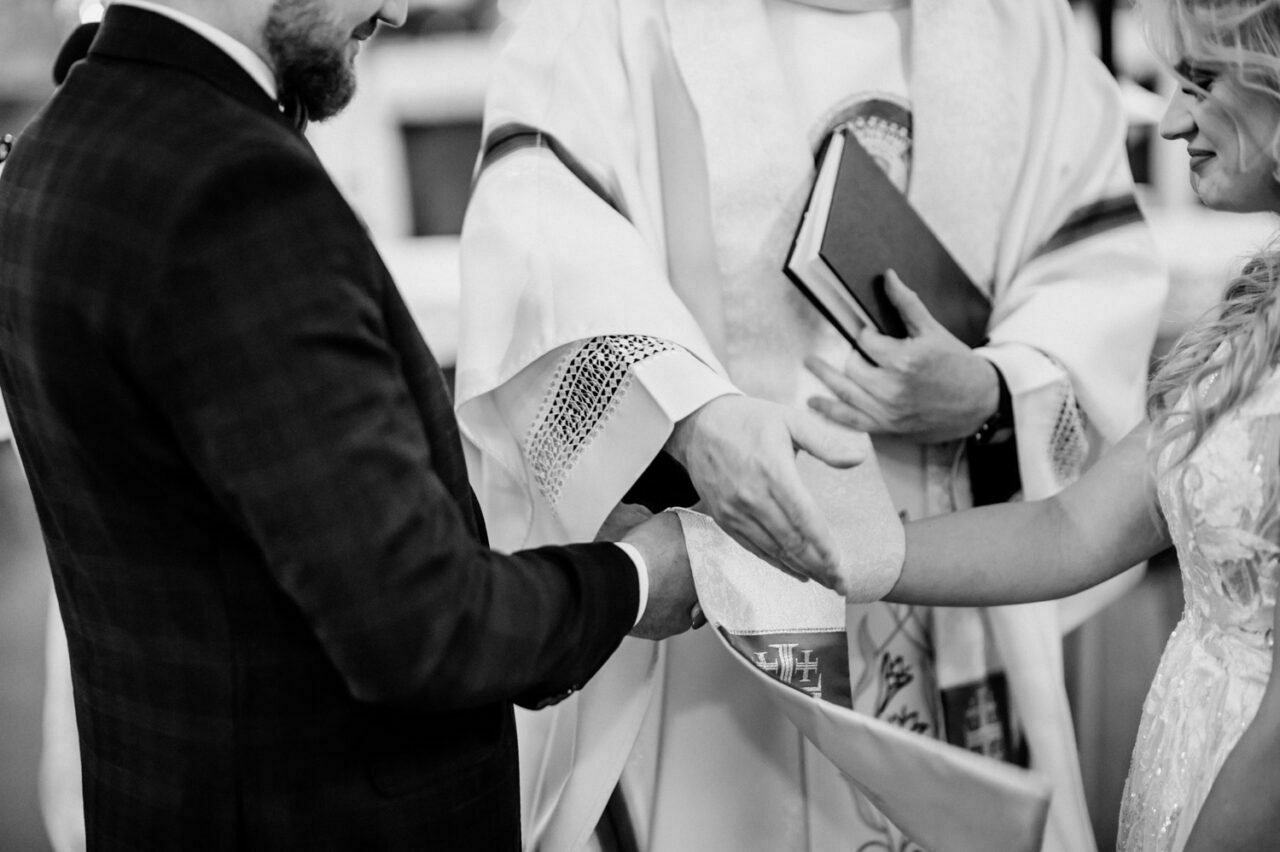 ksiądz przewiązuje dłonie pary młodej stułą