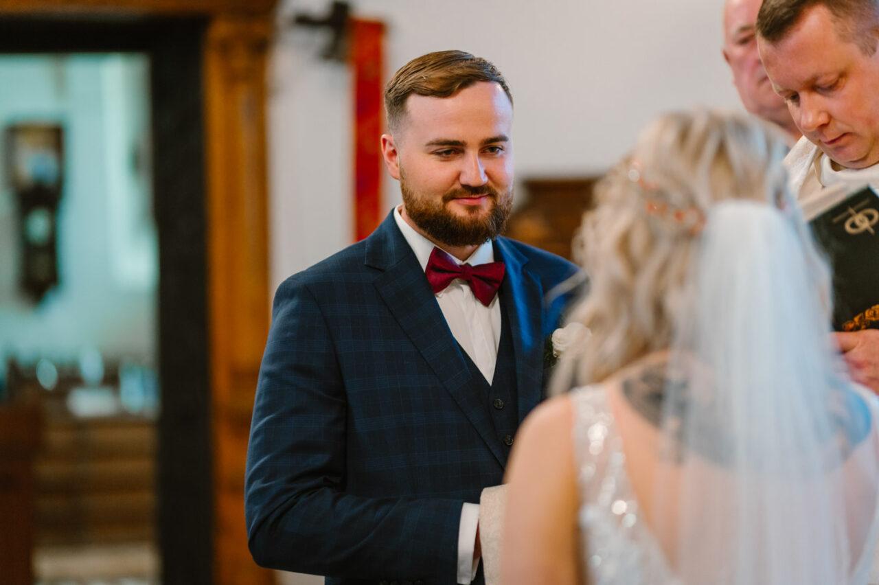 pan młody podczas przysięgi ślubnej w katedrze w Zamościu