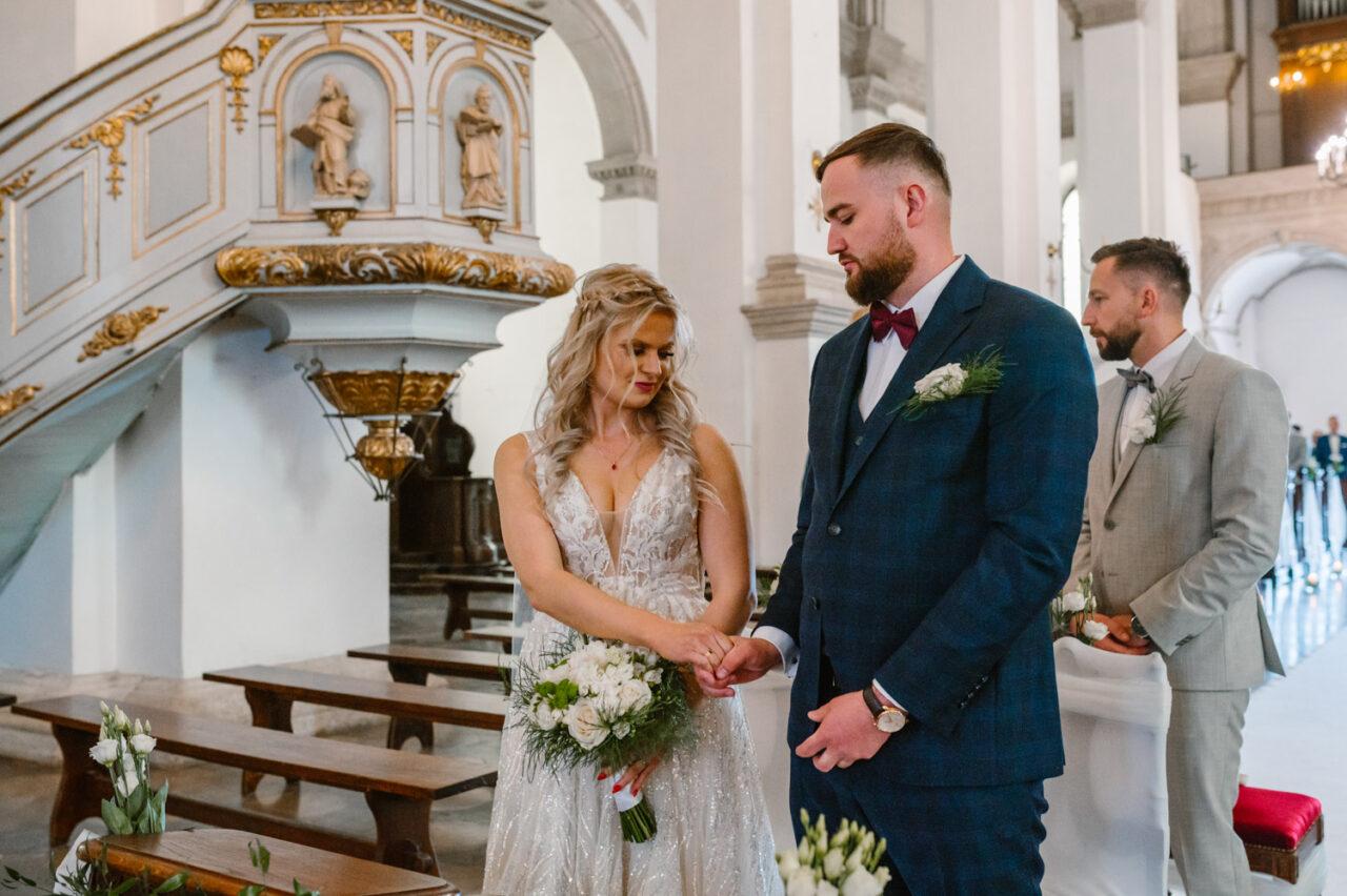 para młoda przekazuje sobie znak pokoju podczas ślubu w Zamościu