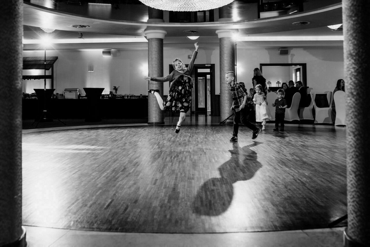 dzieciaki tańczą i skaczą na weselnym parkiecie
