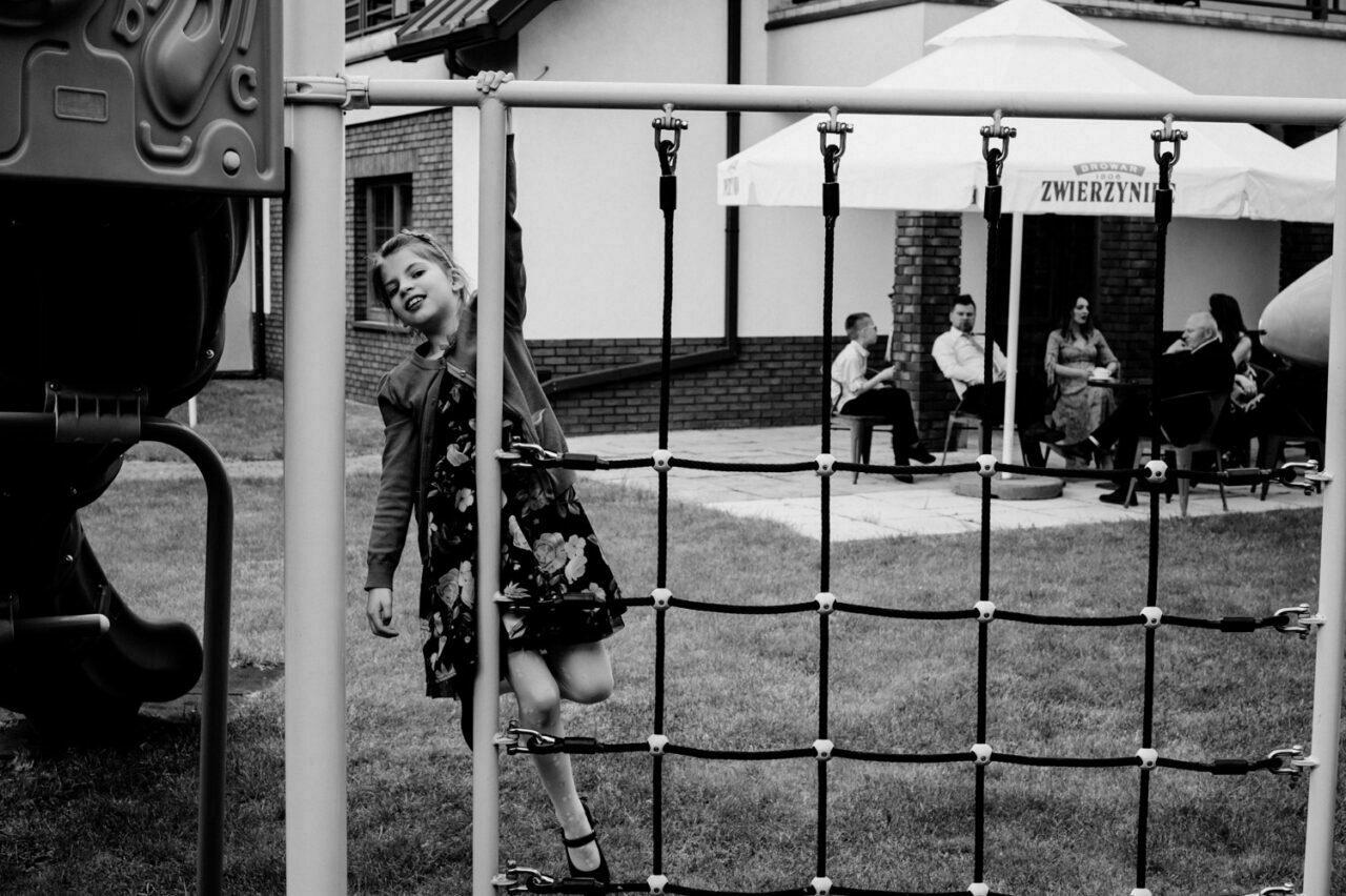 dziewczynka wspinająca się na placu zabaw i rozmawiający goście w tle