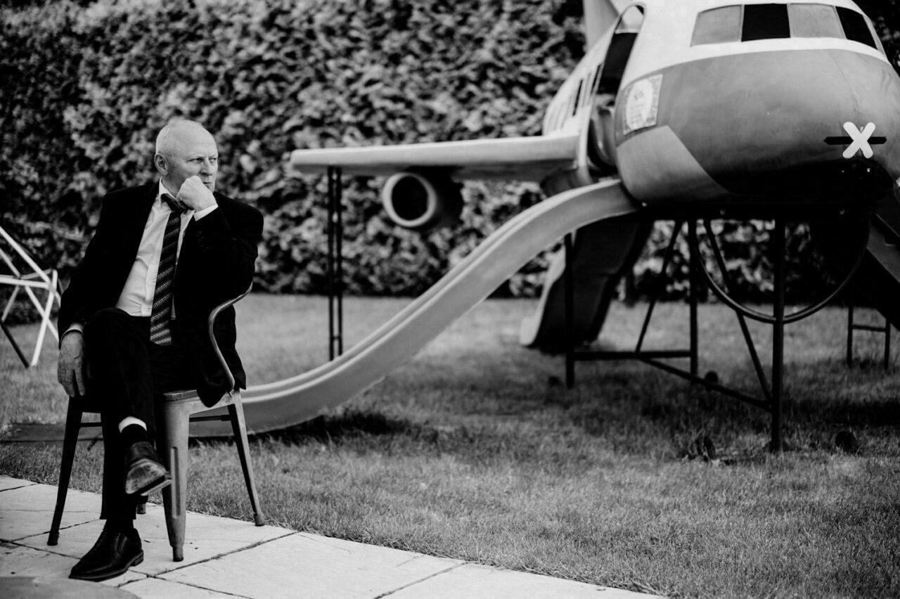 zadumany mężczyzna siedzi na krześle i patrzy w stronę samolotu