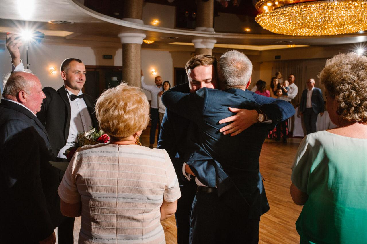 pan młody przytula rodziców na weselu w Zamościu