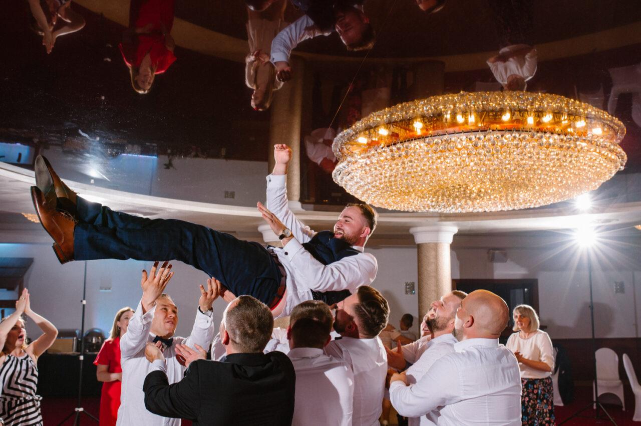 goście podrzucają pana młodego podczas wesela w Zamościu