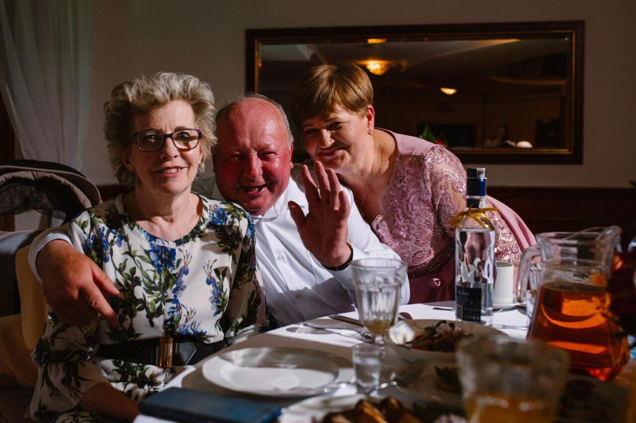 portret starszego mężczyzny i kobiet przy stole weselnym