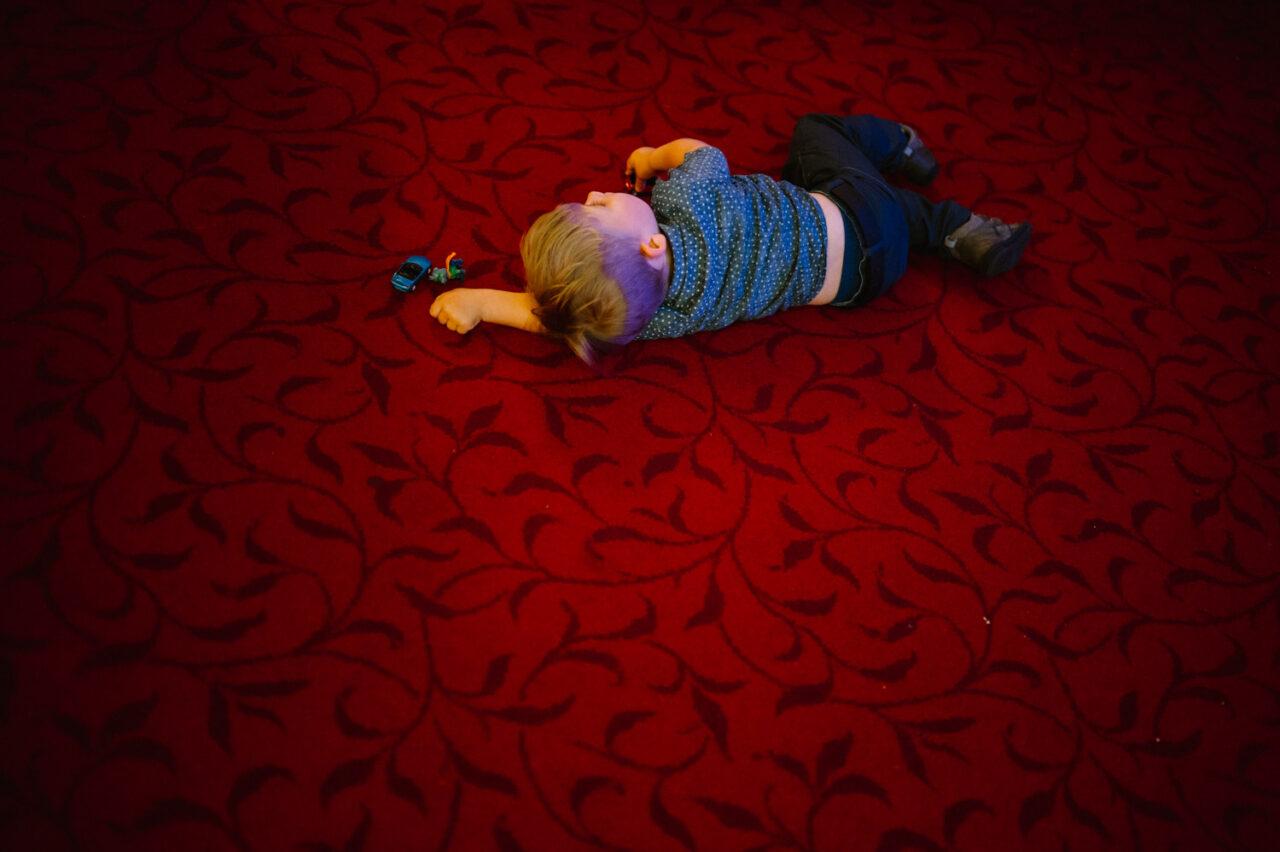dziecko leżące na dywanie z zabawkami