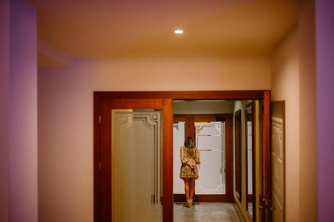 kobieta tyłem podgląda widok zza drzwi
