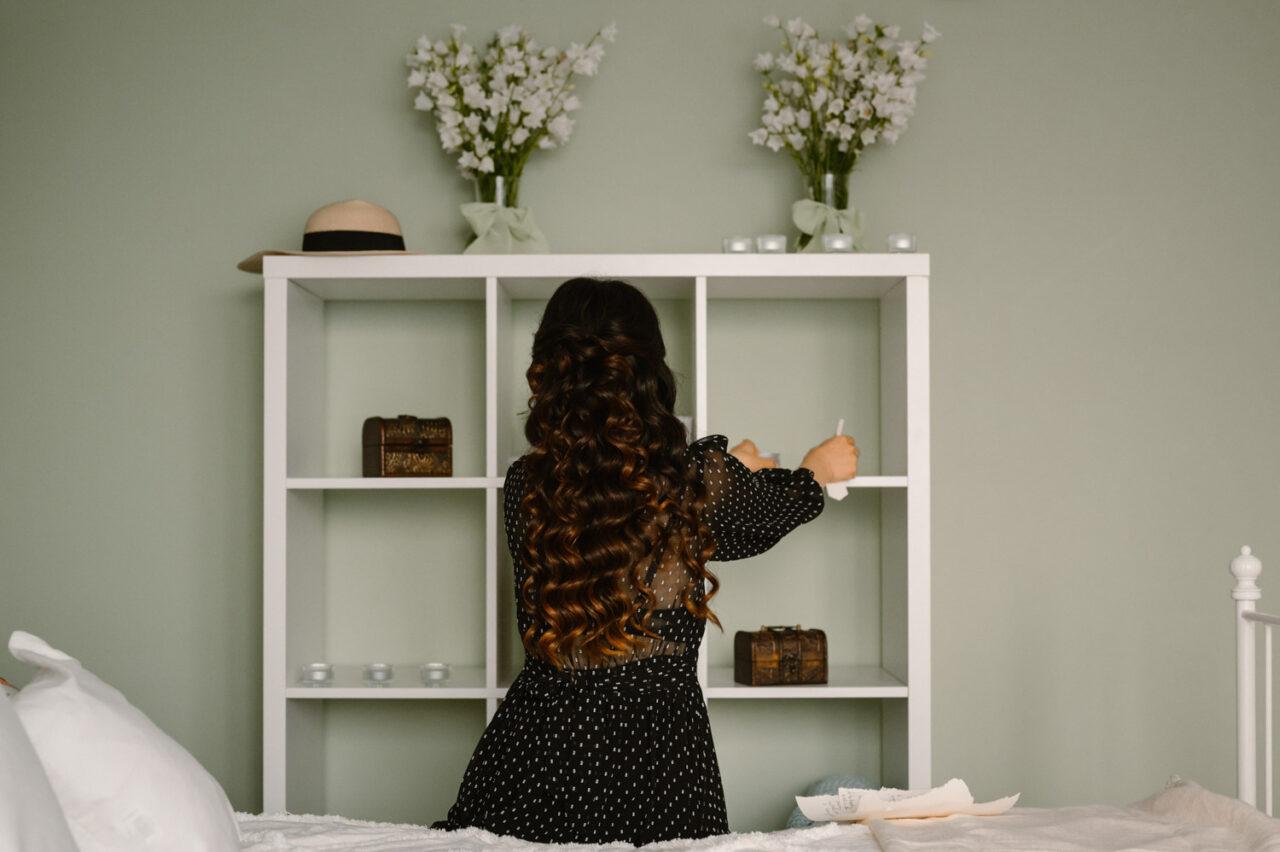 długowłosa dziewczyna układa przedmioty na regale