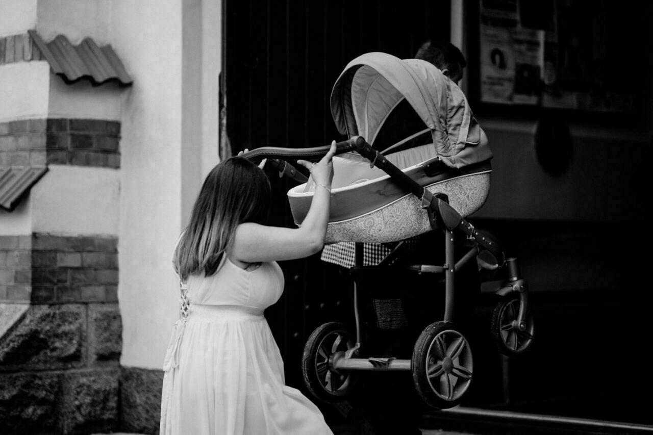 kobieta dźwiga wózek dziecięcy