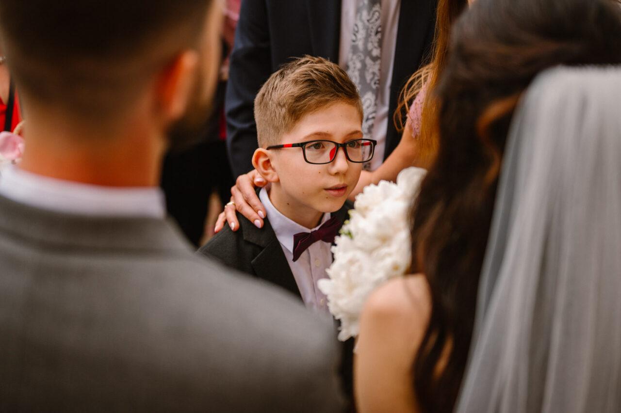 chłopiec składający życzenia parze młodej