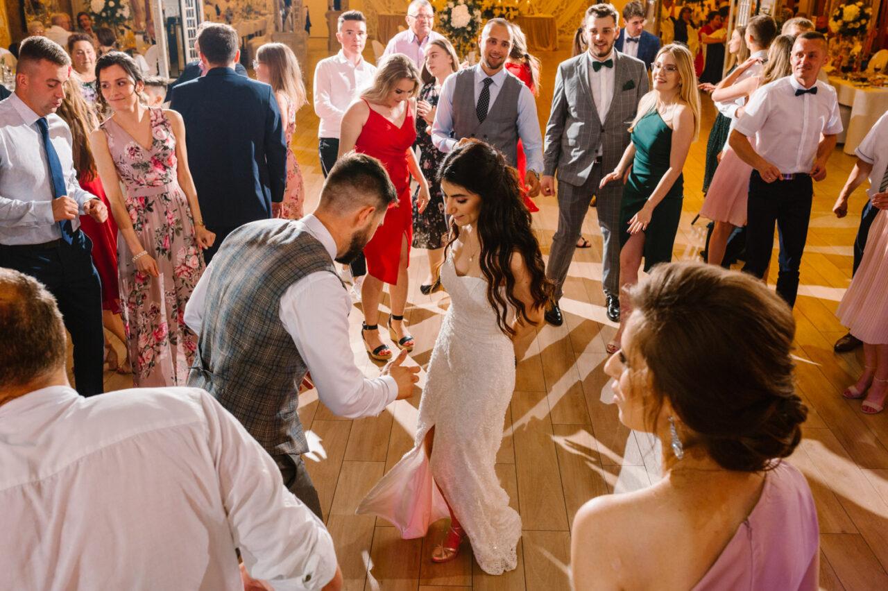 para młoda i goście tańczą w hotelu drob