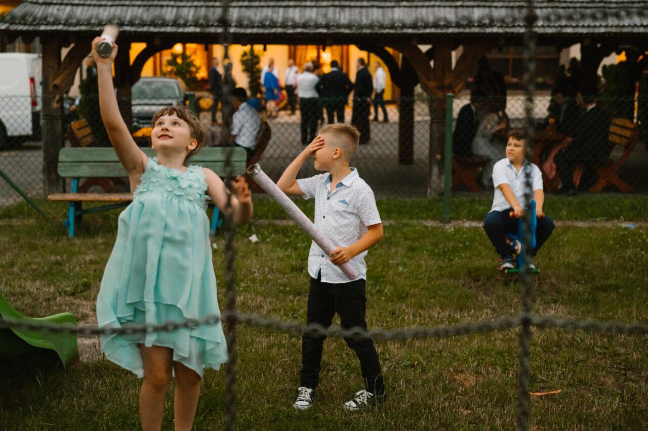 dzieciaki ganiające za owadami o zmierzchu