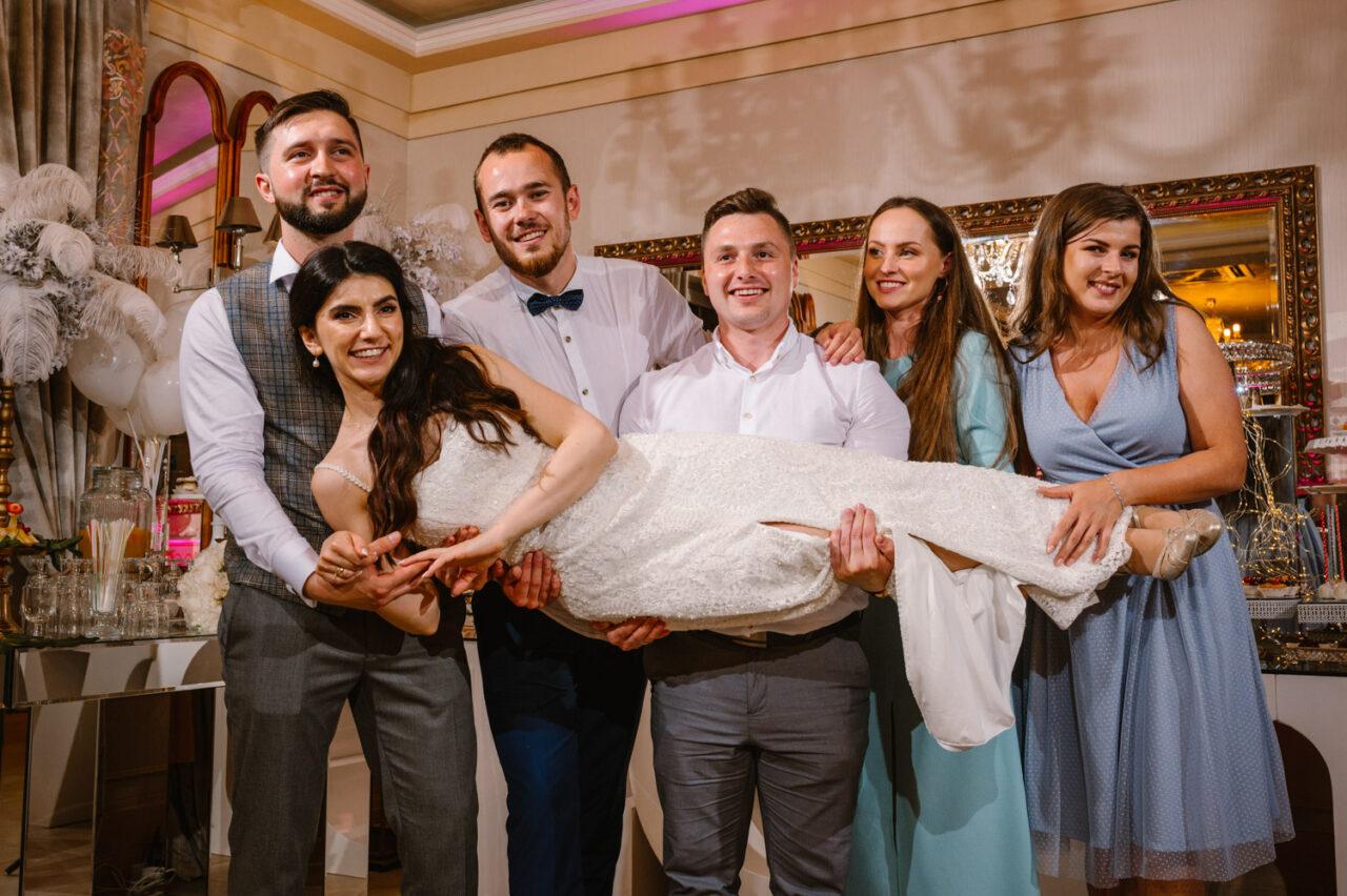 wesoły portret gości weselnych unoszących pannę młodą