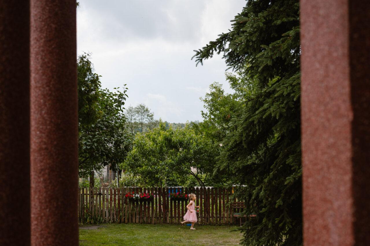 dziewczynka biega po ogrodzie