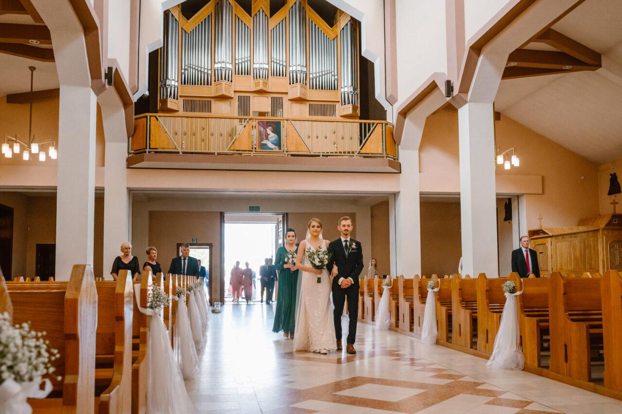 para młoda idzie pod ramię na ślub