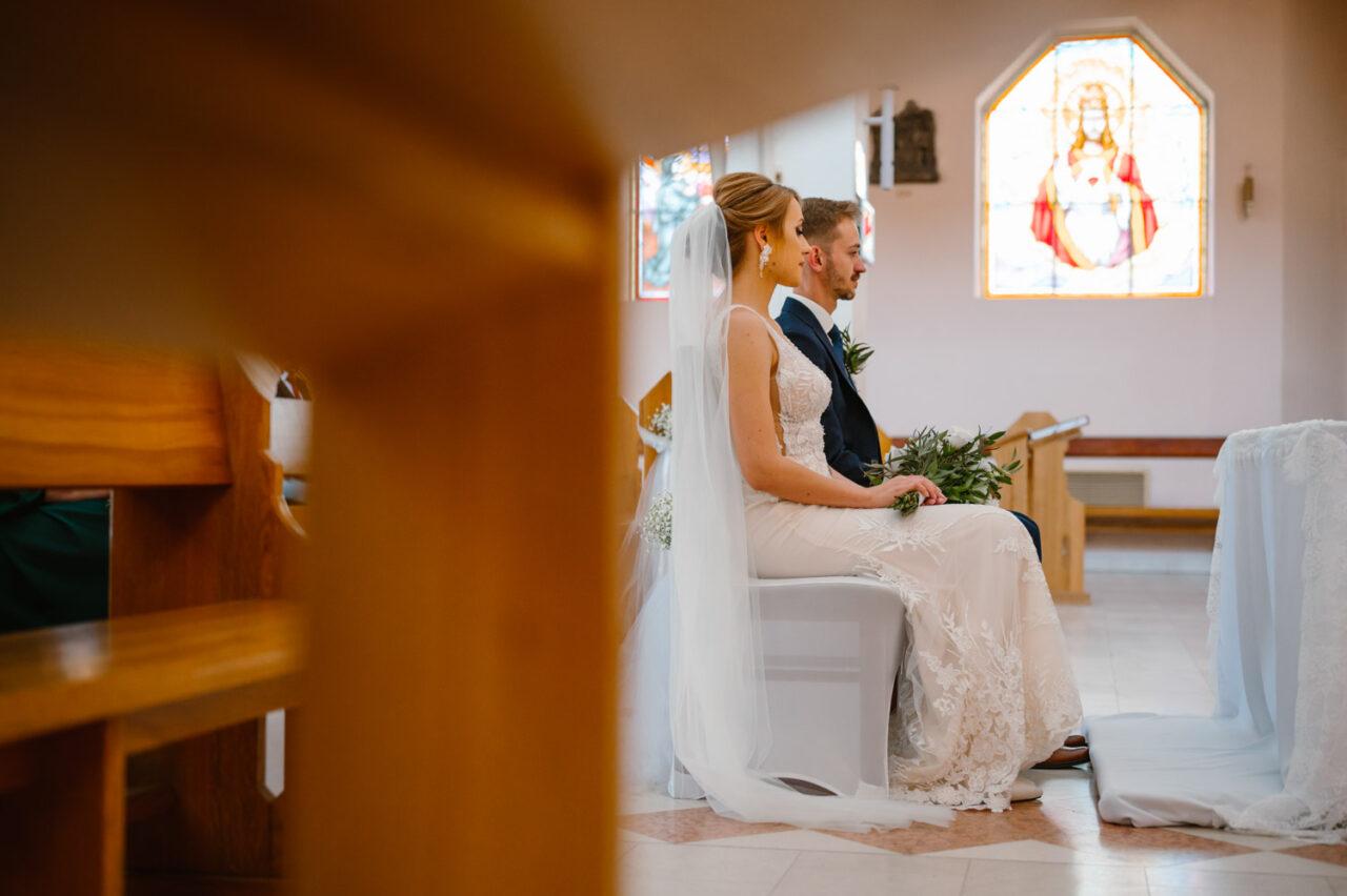 młoda para siedzi w kościele