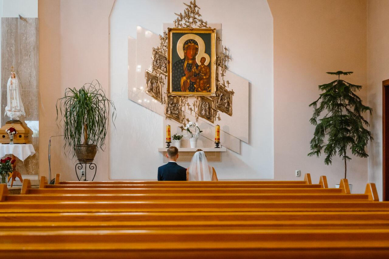 para młoda modli się przed obrazem Matki Bożej