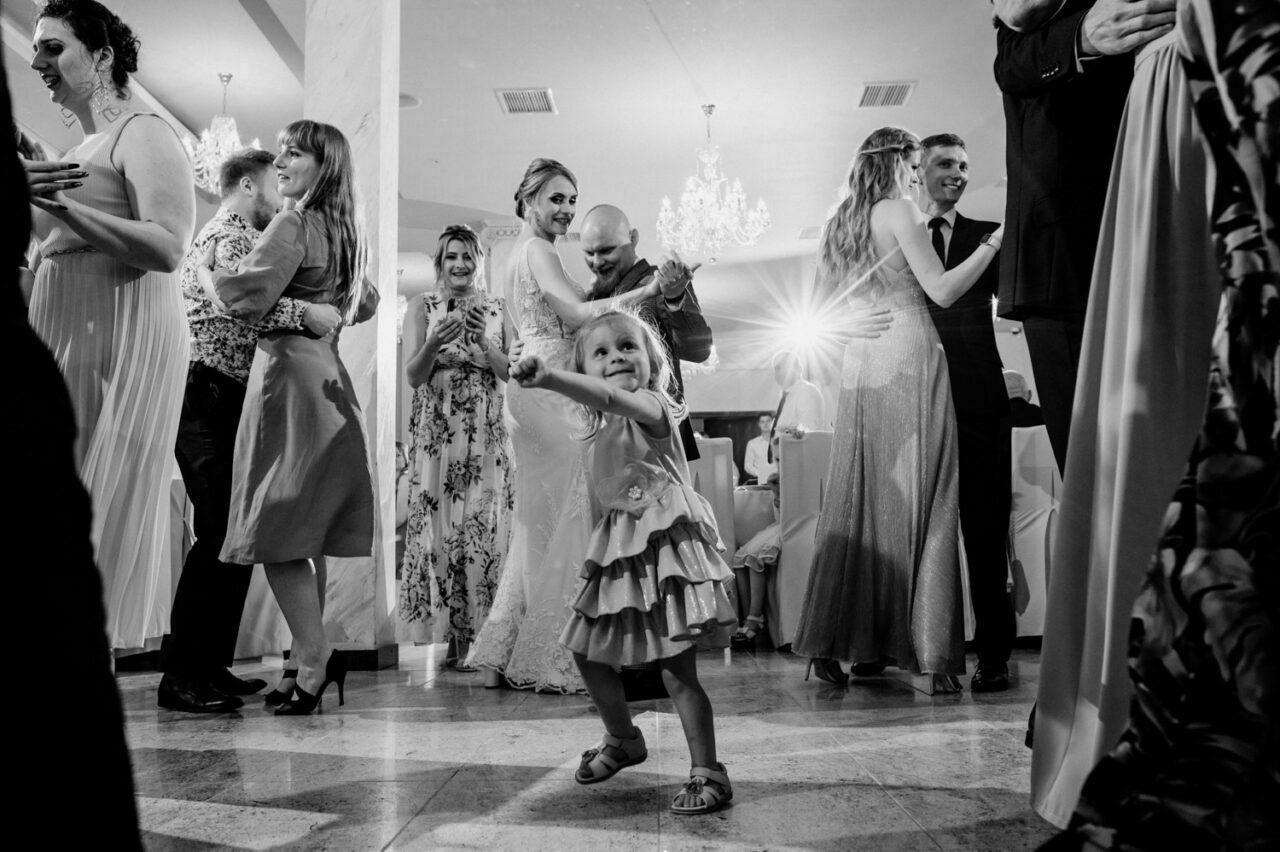 dziewczynka i goście tańczą na weselu